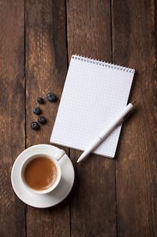 Caderno com uma caneta ao lado de uma chávena de café