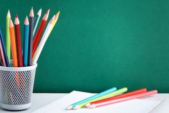 Caderno e lápis coloridos com fundo negro