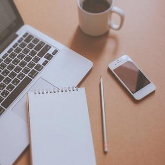 Caderno e laptop com telefone inteligente no local de trabalho com xícara de café, filtro retro tonificado