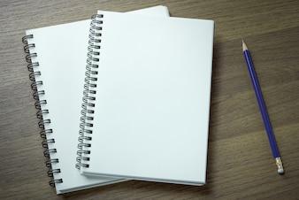 Caderno espiral em branco e lápis em fundo de madeira escura
