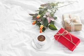 Café da manhã com um presente, flores e chocolates