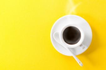 Café expresso em copo de vapor quente de cerâmica branca pequena em fundo amarelo vibrante. Mínimo alimento conceito de energia da manhã.
