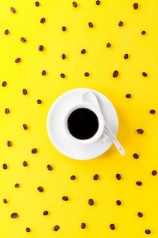 Café expresso em pequeno copo de cerâmica branca com muitos grãos de café em fundo amarelo vibrante.