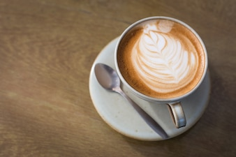 Café Hot Latte em um copo e laptop na mesa de madeira