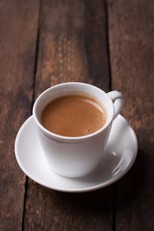 Café no copo de porcelana na tabela de madeira