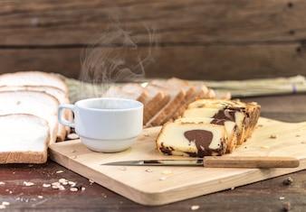 Café quente com bolo e pão na mesa de madeira