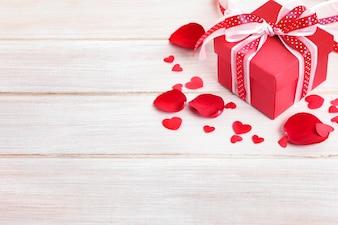 Caixa de presente do Valentim e pétalas de rosa na placa de madeira branca