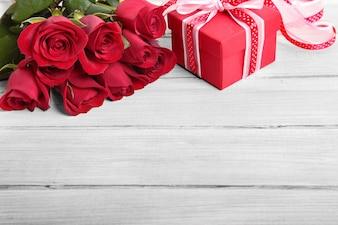 Caixa de presente do Valentim e rosas vermelhas na placa de madeira branca