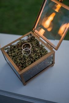 Caixa de vidro com anéis de casamento fica na mesa branca