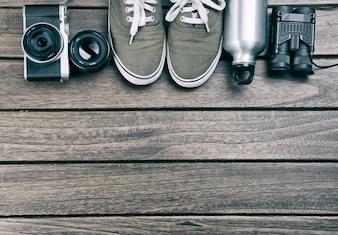 Câmera, lente, binóculos, sapatos de lona, garrafa de esportes na mesa de madeira retro