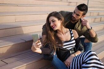 Capturar momentos brilhantes. Pares loving novos alegres que fazem o selfie na câmera ao estar ao ar livre.