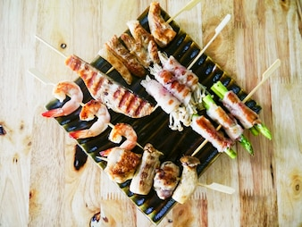 Carne de frango frito e churrasco de frutos do mar com legumes em espetinhos de madeira em um molho de prato. vista do topo