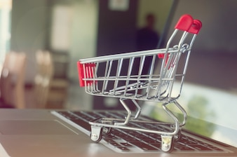 Carrinho de compras pequeno com laptop para compras on-line conceito