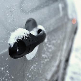 Carro de Inverno, o conceito de passeio de carro de inverno. Glacê na alça do carro.