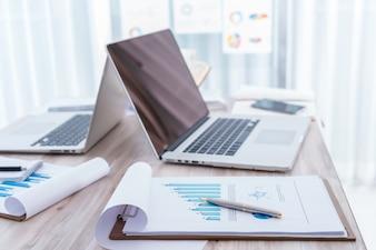 Cartas financeiras na tabela com portátil