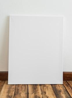 Cartaz branco encostado a uma parede