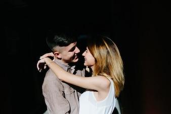 Casal abraçando na rua ensolarada