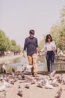 Casal andando de mãos dadas com um parque com pombos