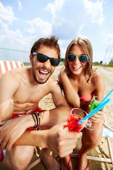 Casal bebendo e rindo na praia