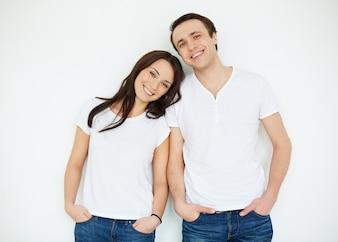Casal com camisas brancas e calças de brim