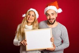 Casal com um chapéu de Santa que prende uma placa em branco no fundo vermelho