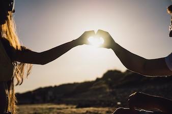 Casal formando coração com as mãos