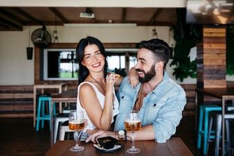 Casal no bar rindo com cerveja
