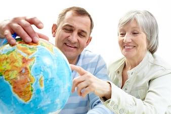 Casal procura o mapa do mundo para a próxima viagem
