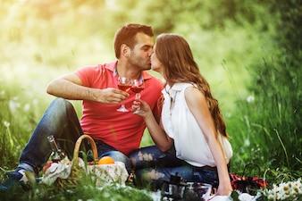 Casal se beijando e segurando copos de vinho