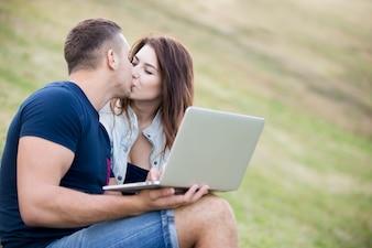Casal se beijando na grama com um portátil