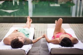 Casal segurando as mãos e descansando perto da piscina