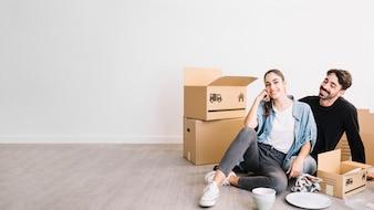 Casal sentado no chão em um novo apartamento