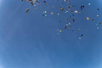 Céu azul com papéis coloridos