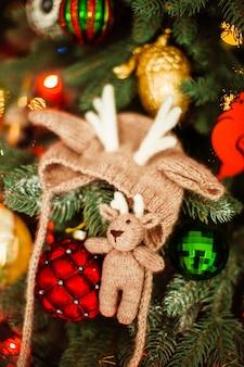 Chapéu bonito de bebê e brinquedos na árvore do Ano Novo
