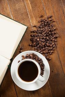 Chávena de café com grãos de café e livro