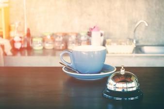 Chávena de café com sino e café quente na cafeteria
