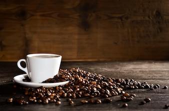 Chávena de café com uma pilha de grãos de café