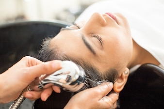 Close-up da jovem mulher relaxada no salão de cabeleireiro