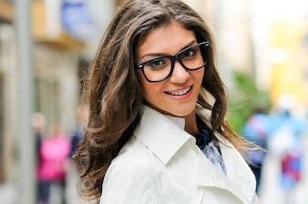 Close-up da mulher bonita com vidros e sorriso grande