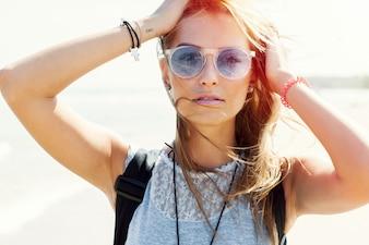 Close-up da mulher com óculos de sol aprecia ao ar livre