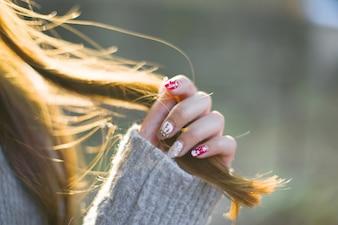 Close-up da mulher com unhas pintadas, tocando seu cabelo