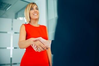 Close-up da mulher de negócios de sorriso que dá um aperto de mão