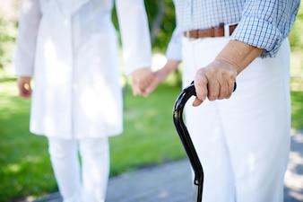 Close-up da mulher idosa com vara de passeio