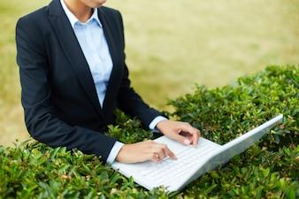 Close-up da mulher que trabalha com portátil ao ar livre