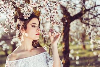 Close-up da noiva que cheira uma flor