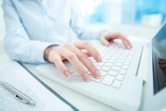 Close-up da secretária com as mãos sobre o teclado