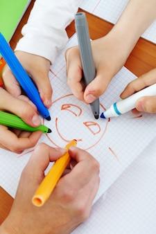 Close-up das mãos de desenho com marcadores coloridos