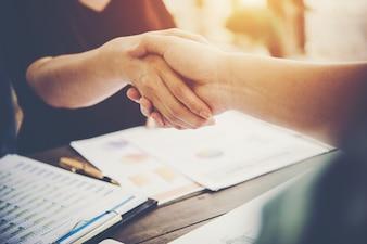 Close-up de dois empresários apertando as mãos enquanto está sentado no local de trabalho.