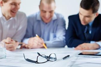 Close-up de óculos com colegas de trabalho fundo borrado