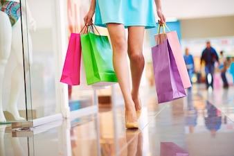 Close-up de uma mulher segurando sacolas de compras